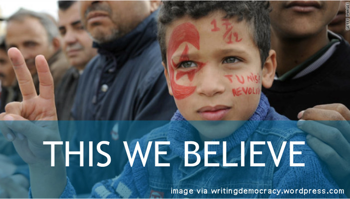 This We Believe: Image of young boy at protest with red paint on his face and fingers held up in a peace sign.
