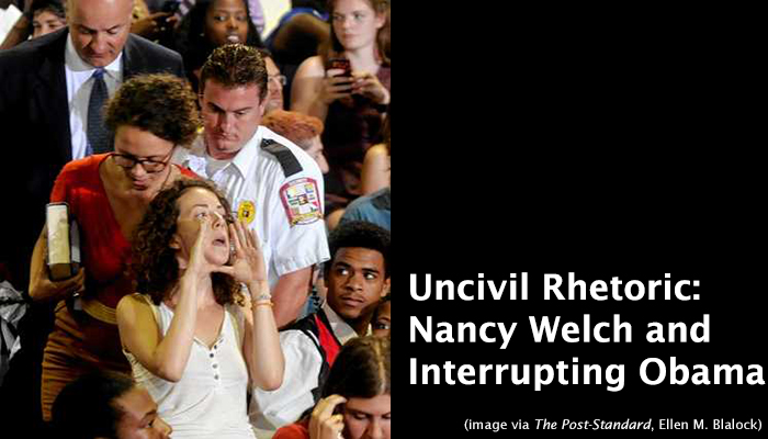 Image from August 22nd Interruption of Obama at Henninger High School in Syracuse. Amelia Ramsey-Lefevre shouts through cupped hands as she and Ursula Rozum are escorted out of the gymnasium.