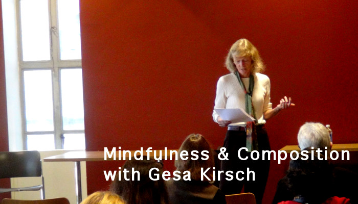 Image shows Gesa Kirsch reading at the Rhetorical Listening Symposium. She stands in front of a seated audience.