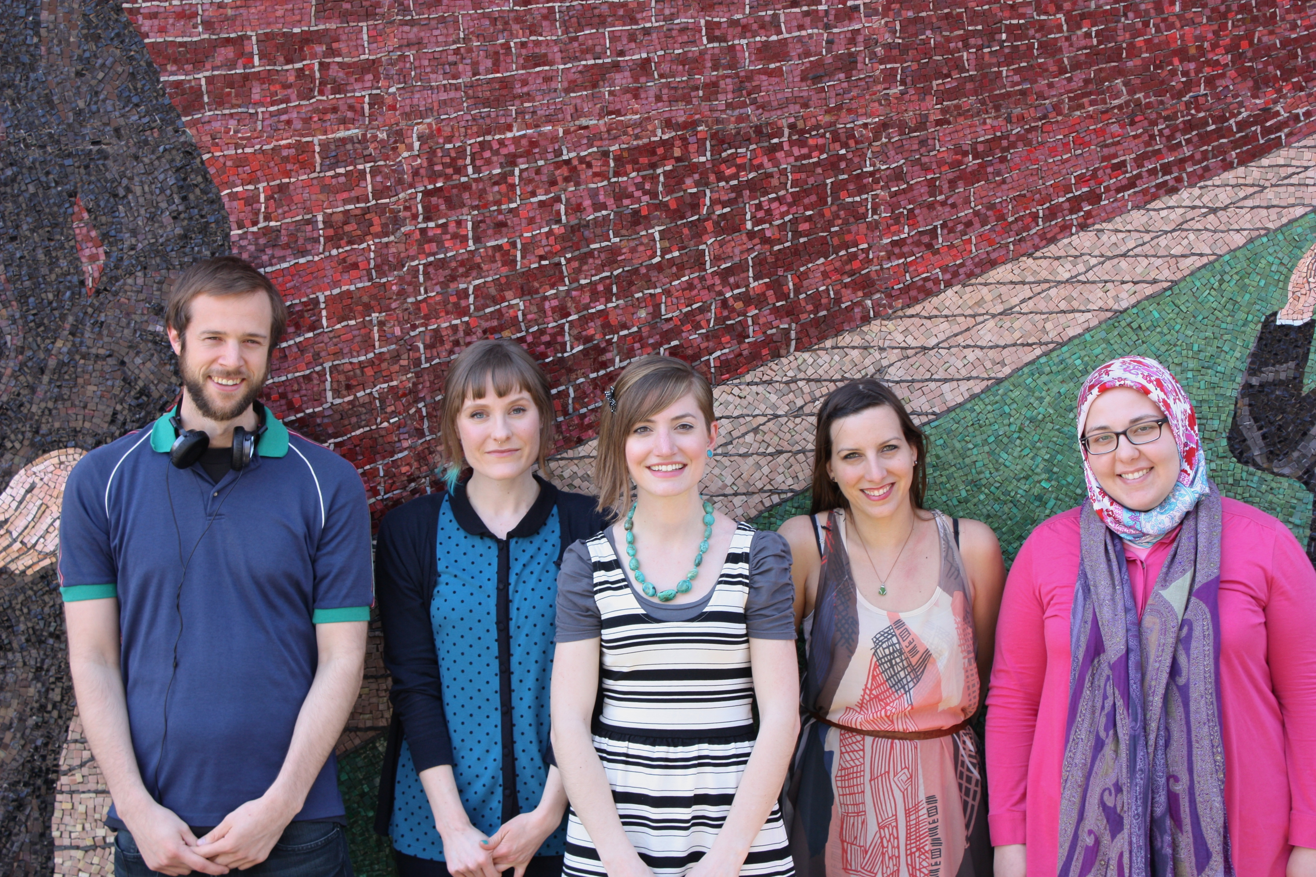 Image of the TRL podcasting group. In order from left to right, Ben, Jana, Allison, Karrieann, and Tamara stand in front of a mural that depicts red bricks, a sidewalk, and green grass.