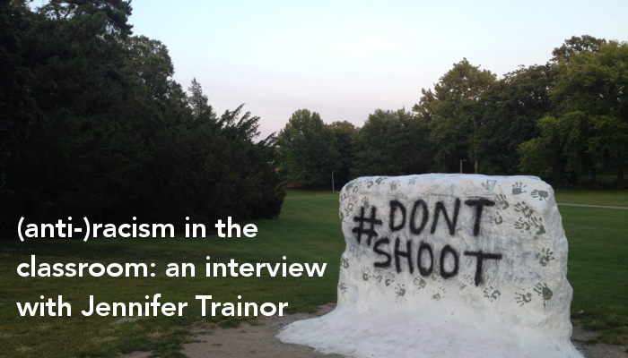 "The image features The Rock at MSU, spray painted white with black handprints and bold text that reads #DONTSHOOT. There are green trees in the background a pale blue and pick sky at dusk. The text over the image reads, ""(anti-)racism in the classroom: an interview with Jennifer Trainor"""